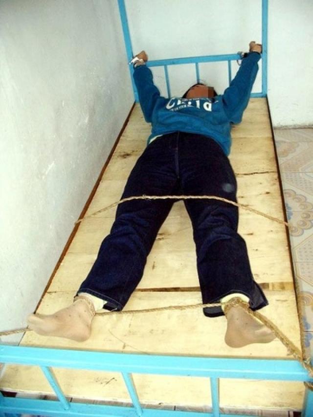 Руки и ноги раздетого догола заключенного привязываются к углам кровати, на которой вместо матраца деревянная доска с вырезанным отверстием, под которое подставляется ведро для испражнений. В таком положении человек находится непрерывно от нескольких дней до недель.