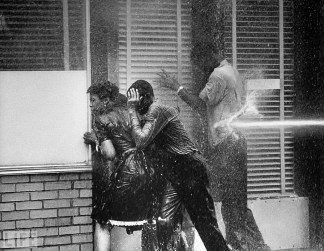 Приветствие мира пожарными брандспойтами (Meeting peace With fire hoses, Charles Moore, 1963). Разгон мирного митинга против сегрегации в Берменгеме, США.