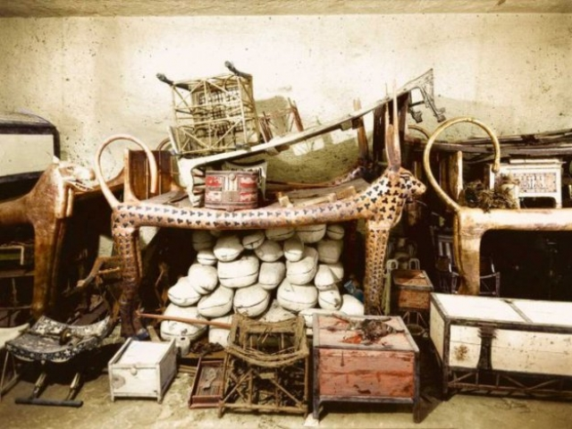 Несмотря на следы того, что в гробницу дважды наведывалась древние грабители, содержимое первой комнаты оставалось практически нетронутым. Гробница была напичкана тысячами бесценных артефактов. На фото: декабрь 1922 года. Церемониальное ложе в форме Небесной коровы, в окружении припасов и других объектов в передней комнате гробницы.