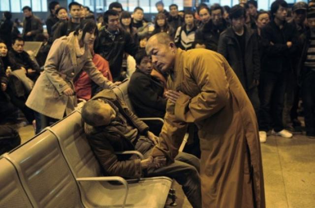 Монах рядом с пожилым человеком, который внезапно умер, ожидая поезда в Шаньси Тайюань, Китай.