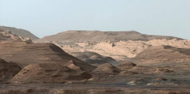 На переднем плане, примерно в трех километрах от ровера, находится длинных хребет, изобилующий окидом железа.