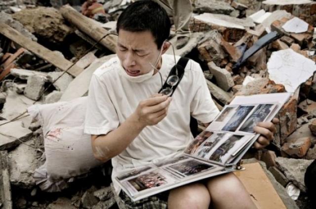 Парень смотрит семейный альбом, который нашел в щебне его старого дома, после землетрясения в Сычуани.