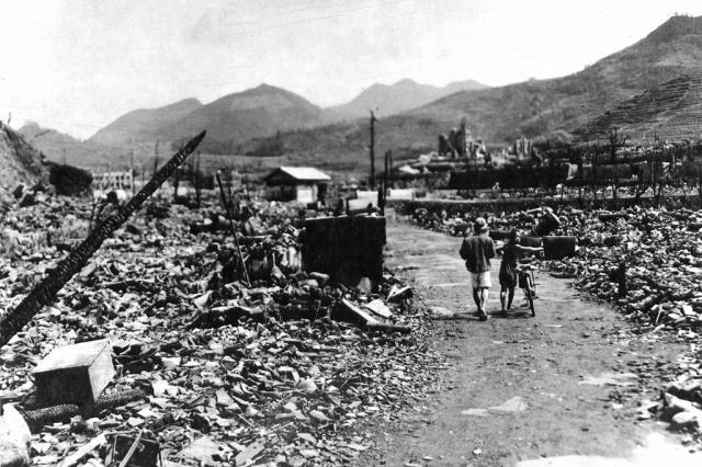 Японские мирные жители идут по улице разрушенного Нагасаки.