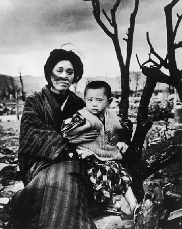 Мать с ребенком посреди разрушенного города.