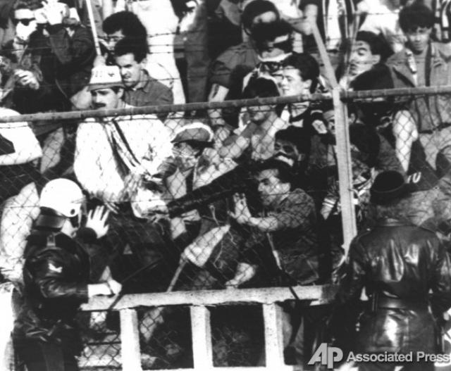 Толпа надавила на разделяющий сектора кирпичный барьер, и он обрушился, не выдержав людского напора.
