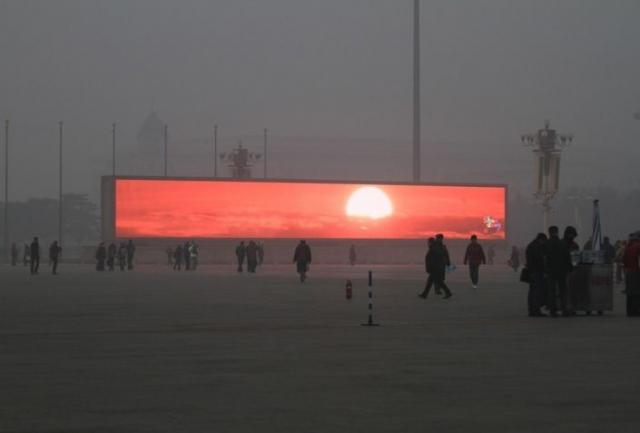 В Пекине жители вынуждены любоваться рассветом на экране из-за ужасного смога. На самом деле экран является частью рекламного щита и крутится круглый год, независимо от наличия смога.