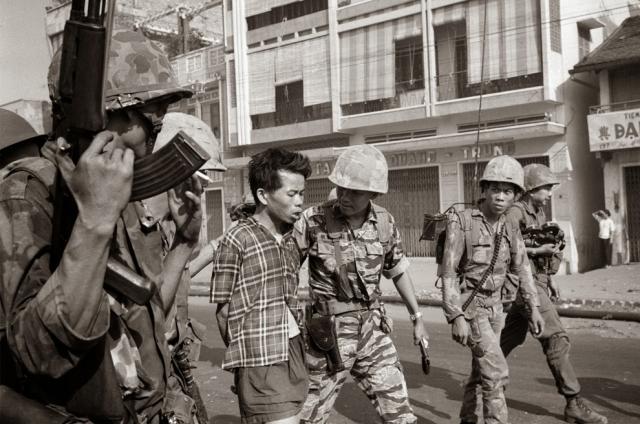 На глазах журналистов двое южновьетнамских морских пехотинцев подвели пленного к генералу. Партизан в клетчатой рубашке и черных шортах со связанными руками стоял молча, опустив глаза к земле.