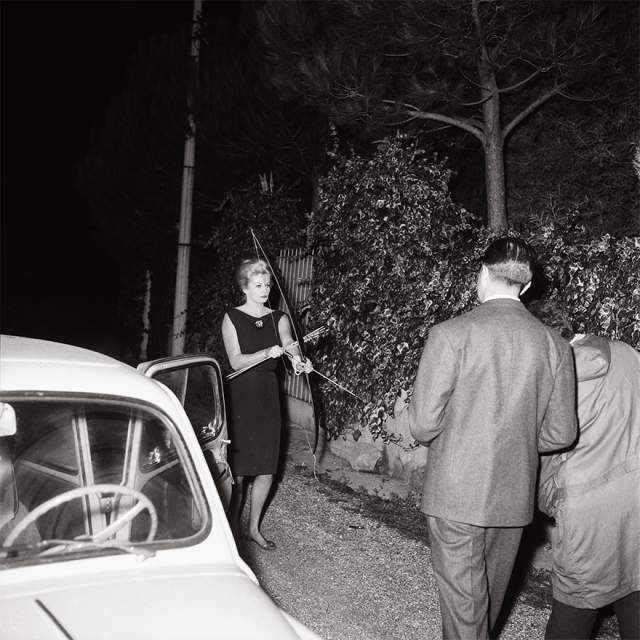 """Тот самый звездный для Квинто снимок, где Анита Экберг угрожает ему луком и стрелами. Так звезда культового фильма Федерико Феллини """"Сладкая жизнь"""" (La Dolce Vita) защищала свою приватность. 20 октября 1960 года."""