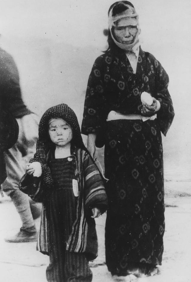 Женщина и ее сын, держащие в руках рис, на следующий день после бомбардировки юго-западнее центра взрыва на расстоянии 1 мили от него.