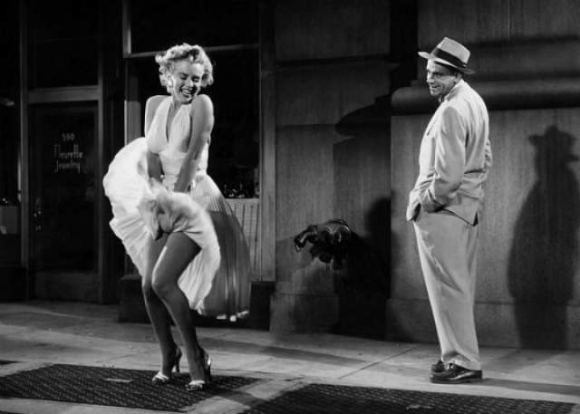 """Мэрилин Монро в развевающемся платье. Фотография была сделана во время съемок фильма """"Зуд седьмого года"""". Секс-символ стоит на тротуаре, и теплый воздух, выходящий из нью-йоркской подземки, приподнял подол ее белоснежного легкого платья."""