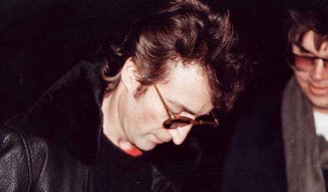 А это Джон Леннон за пару часов до того, как его убьет Марк Дэвид Чэпмэн, человек на фоне.
