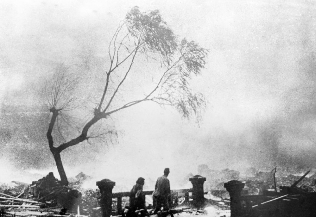 Люди среди руин на фоне бушующего огня на заднем плане, 9 августа 1945 года.