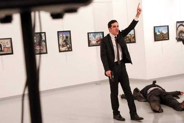 Преступник в деловом костюме и галстуке прошедшей на выставку по документам полицейского, расстрелял в спину у стойки перед микрофоном дипломата.