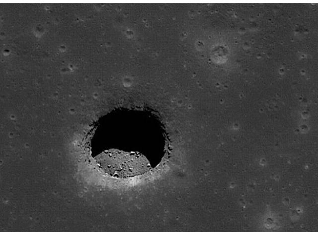 """А это кратер, снятый на обратной стороне Луны, который скорее похож на дыру в поверхности. Этот тип кратеров назвали """"кратерами обвала"""", а уфологи подозревают, что это ни что иное, как остатки подземных лунных сооружений."""