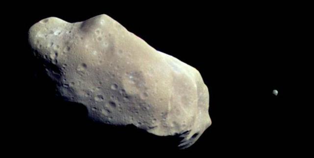 """Ида и Дактиль. Это цветное изображение асетроидов было снято фотосистемой, установленной на космическом аппарате НАСА """"Галилео"""". Снимок было сделан 28 августа 1993 г."""