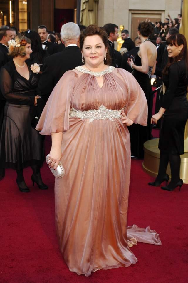 """Правда, несмотря на тренд """"бодипозитив"""", вес звезды однажды повлиял на ее жизнь в плохом смысле. Дело в том, что платья для """"Оскара"""" зачастую выдаются напрокат в подиумном размере XS. И в 2012 году Мелиссе Маккарти отказали сразу шесть брендов. На фото она в платье от Marina Rinaldi, у которой нашлось кое-что симпатичное на нетипичную фигуру."""