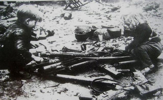 Немецкие дети, играющие с брошенным оружием (винтовки, пистолеты-пулеметы) на одной из улиц Берлина.