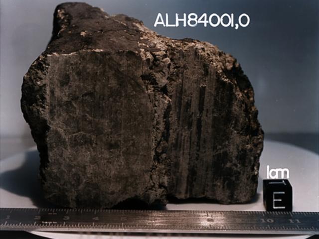 17. Метеорит АLH84001 Под этим именем скрывается, пожалуй, самый известный из 34 марсианских метеоритов, найденных на Земле. Его обнаружили 27 декабря 1984 года в горах Алан Хиллс в Антарктиде. Согласно проведенным исследованиям, возраст инопланетного тела составляет от 3,9 до 4,5 миллиардов лет. Метеорит, вес которого равен 1,93 кг, упал на Землю около 13 тыс. лет назад. Существует гипотеза, согласно которой он откололся от поверхности Марса во время столкновения планеты с крупным космическим телом.