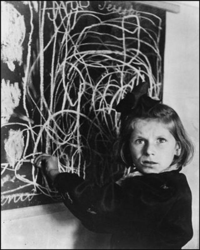 """Польша - девочка Тереза, выросшая в концентрационном лагере, рисует """"дом"""" на доске. 1948."""