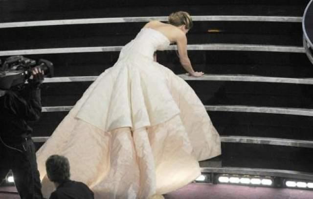 """Дженнифер Лоуренс, которая вышла получать своего первого """"Оскара"""" в 2013 году, упала, запутавшись в пышном белом платье от Dior. Однако при бурной поддержке зала, который аплодировал стоя, она гордо поднялась на сцену за статуэткой за лучшую женскую роль в фильме """"Мой парень-псих"""". """"Вы хлопаете стоя, потому что я упала? Боже, как неудобно!"""", - сказала актриса, смущаясь."""