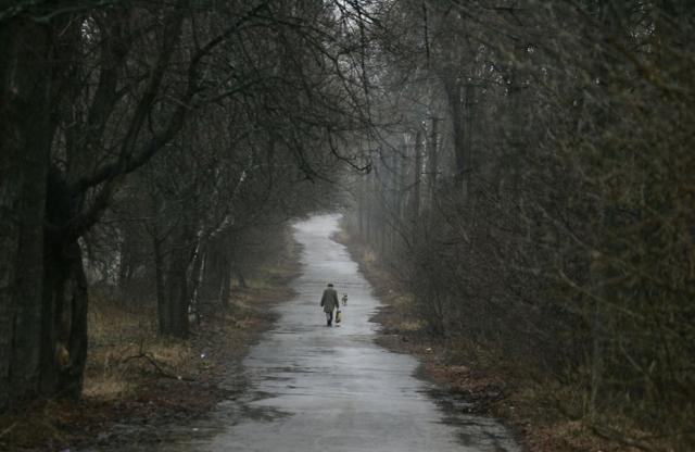 Вот украинец с собакой на улице города-призрака в Чернобыле 13 апреля 2006 года.
