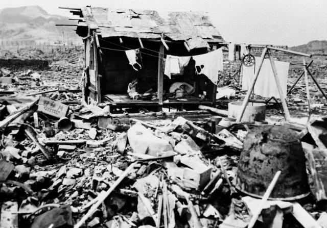 Японская семья ест рис в хижине, построенной на обломках их дома в Нагасаки, 14 сентября 1945 года.