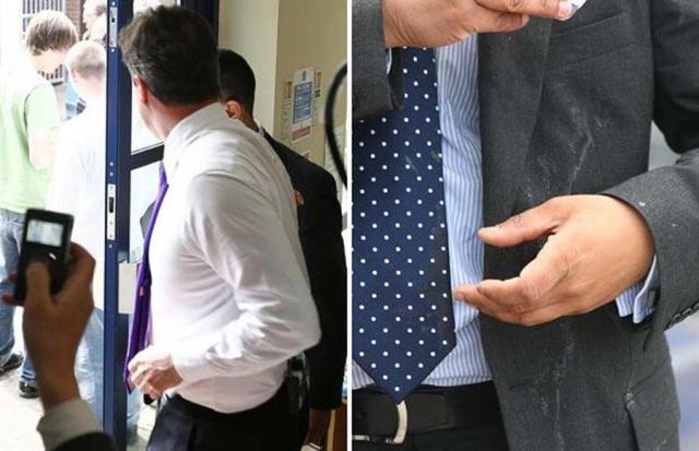21 апреля 2010 тогда еще лидера Консервативной партииВеликобритании Дэвида Кэмерона неизвестный бросил яйцом. На фото: слева, видна часть яичной скорлупы. Справа: офицер полиции убирает яйцо с пиджака Кэмерона.