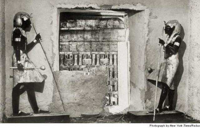 И вот тут исследования были остановлены: Картер решил закрыть гробницу и уехал в Каир для переговоров с египетским правительством. На фото: декабрь 1922 года. Стена погребального покоя охраняется черными статуями Ка.Секретная внутренняя камера гробницы Тутанхамона видна в проломе.