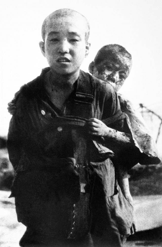 Мальчик несет на спине своего пострадавшего брата. Японская сторона скрывала подобные фото, однако после окончания войны их обнародовали сотрудники ООН.