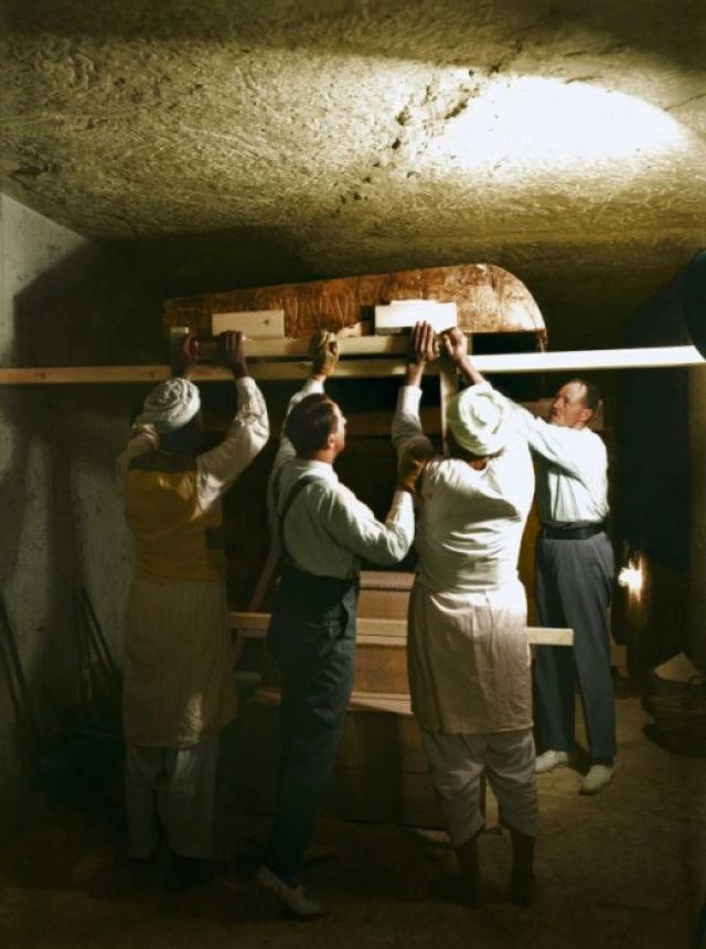 Открыв саркофаг, учёные обнаружили огромный позолоченный рельефный портрет Тутанхамона, который на деле оказался крышкой двухметрового гроба, повторяющей контуры мужской фигуры. На лбу крышки-портрета находились обвитые гирляндой из высохших цветов символы Нижнего и Верхнего Египта – Кобра и Ястреб. На фото: Картер, Каллендер и двое египетских рабочих тщательно разбирают один из золотых ковчегов в погребальном покое.