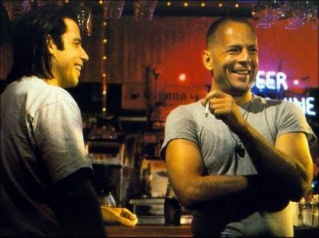 Криминальное чтиво Джон Траволта и Брюс Уиллис над чем-то смеются между сценами.