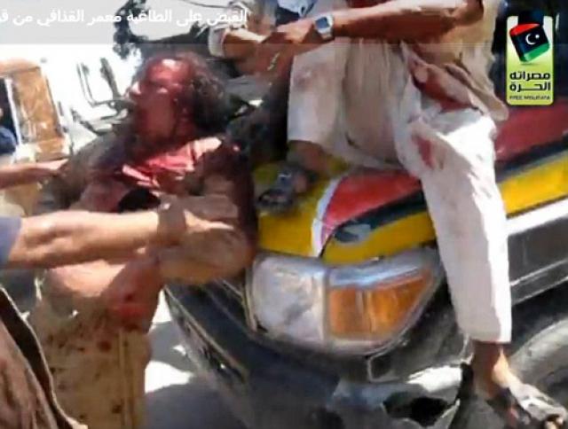 """Повстанцы сумели захватить раненого Каддафи, после чего его тотчас окружила толпа, которая стала издеваться над ним. Люди с криками """"Аллаху Акбар!"""" принялись стрелять в воздух и тыкать в полковника автоматами.Каддафи с залитым кровью лицом повели к автомобилю, где посадили на капот."""