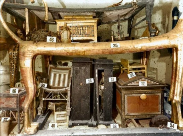Удивлению археологов не было пределов. Здесь находился золотой трон, вазы, ларцы, светильники, письменные принадлежности, золотая колесница. На фото: декабрь 1922 год. Под ложе-львом в передней комнате несколько коробок и сундуков, а также кресло из черного дерева и слоновой кости, которое Тутанхамон использовал в детстве.