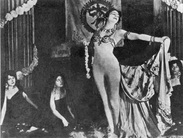 """В конце танцевального номера, исполнявшегося перед узким кругом ценителей на сцене, усыпанной лепестками роз, танцовщица оставалась почти полностью обнаженной (по легенде, """"так было угодно Шиве"""")."""