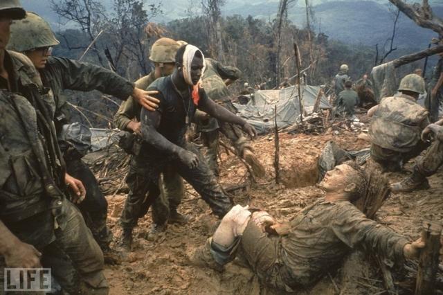 Дотягиваясь (Larry Burrows, 1966). Морские пехотинцы во время войны во Вьетнаме. Темнокожий солдат тянется к своему раненому белому товарищу.