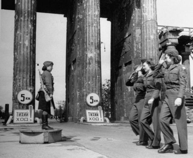 Американские девушки-военнослужащие отдают честь советской регулировщице в Берлине у Бранденбургских ворот.