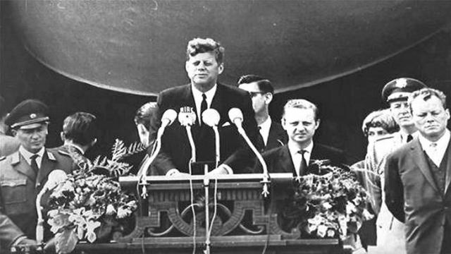 """26 июня 1963 года в своей речи у Берлинской стены в Западном Берлине Кеннеди выразил поддержку берлинцам и жителям ФРГ фразой """"Ich bin ein Berliner"""" . Фраза на немецком увенчала речь, произнесенную на английском."""