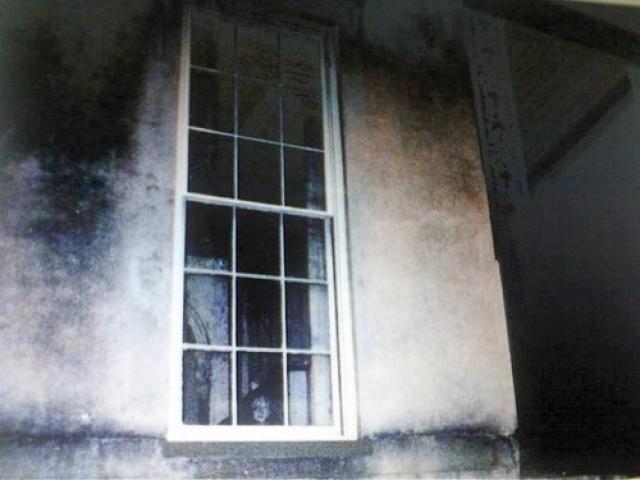 На фотографии запечатлен призрак ребенка, смотрящего из окна известного дома с привидениями на улице Аберкорн, 432, в городе Саванна, США. Легенда гласит, что от теплового удара в доме умерла девочка, привязанная к стулу у окна.