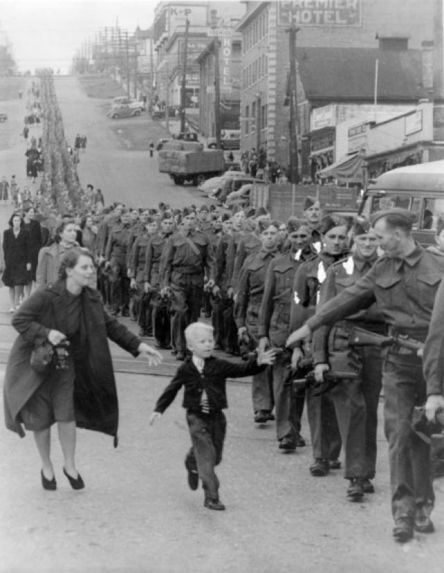 """Фото марша Полка Британской Колумбии. Пятилетний Уоррен """"Уайти"""" Бернард убежал от своей матери к отцу, рядовому Джеку Бернару, с криком """"Подожди меня, папа"""". Фотография получила широкую известность, была опубликована в """"Life"""", висела в каждой школе Британской Колумбии во время войны и была использована в выпусках военных облигаций."""