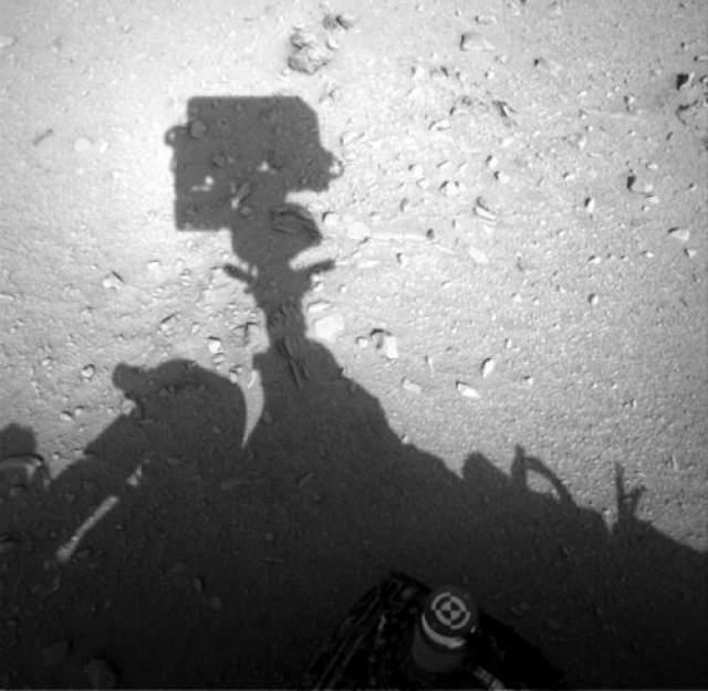 """Загадочную тень многие приняли за фигуру гуманоида или космонавта, находящегося в настоящее время на Марсе. Противники этих версий считают, что на самом деле так причудливо легла тень от робота - выступающие элементы образовали эту занимательную композицию. На фото, сделанном под другим углом, гуманоид пропадает. Но """"рука"""" видна."""