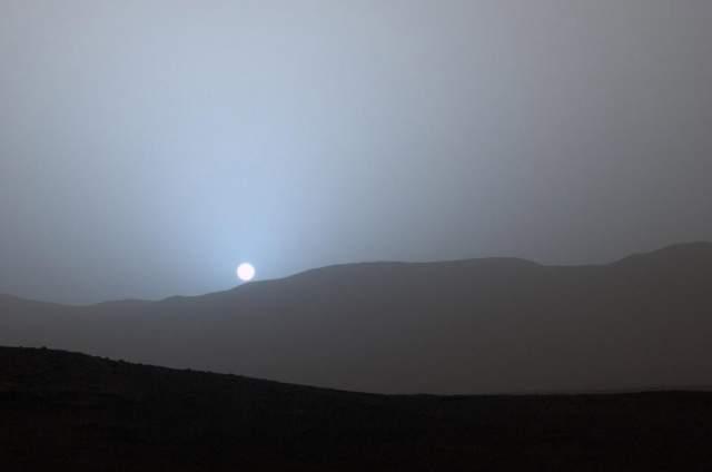 В полдень небо Марса желто-оранжевое. причина таких отличий от цветовой гаммы земного неба - свойства тонкой, разреженной, содержащей взвешенную пыль атмосферы Марса. На Марсе рэлеевское рассеяние лучей (которое на Земле и является причиной голубого цвета неба) играет незначительную роль, эффект его слаб, но проявляется в виде голубого свечения при восходе и закате Солнца, когда свет проходит более толстый слой воздуха. На фото - Марсианский закат, 15 апреля 2015 года.