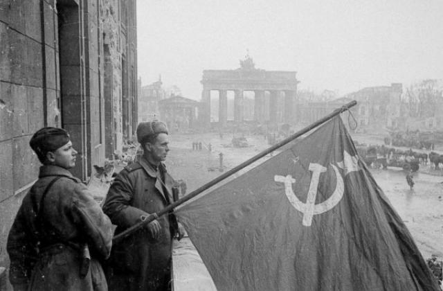Советские военные - рядовой и лейтенант - со знаменем в Берлине на фоне Бранденбургских ворот.