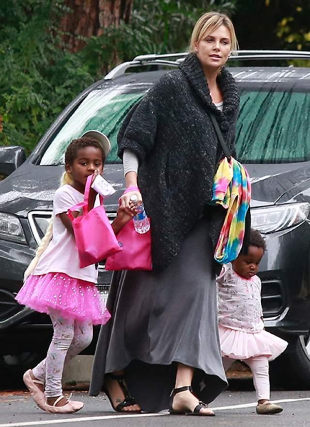 Шарлиз Терон, 42 года. Последние три года эта голливудская звезда совершенно одинока: всю себя она посвятила воспитанию приемных детей — сына Джексона (в розовом платьице) и дочери Август (в белом платьице).