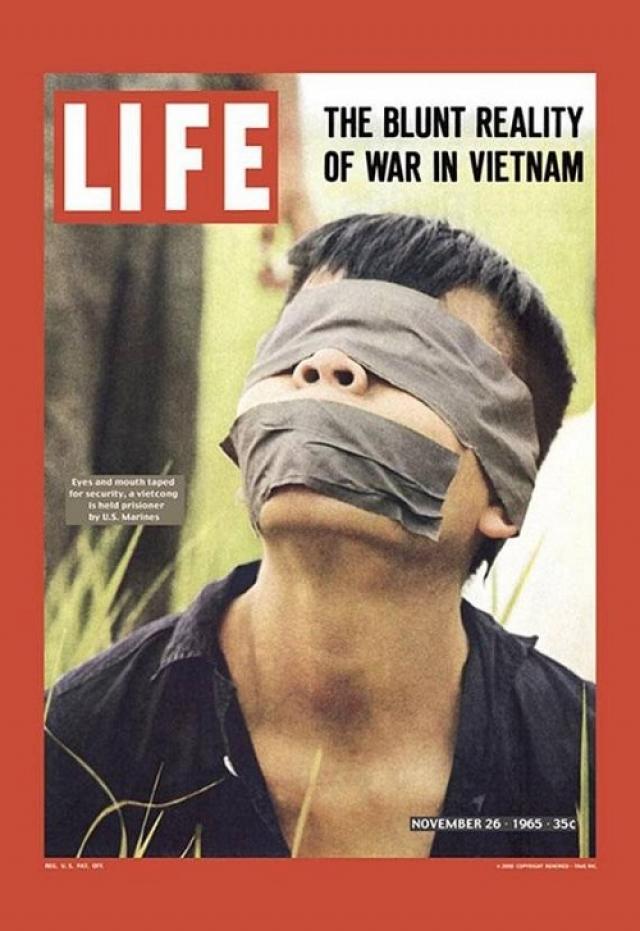 """LIFE, ноябрь 1965. Снимок вьетконговского заключенного с заклеенными глазами и ртом. Через несколько минут после снимка заключенного застрелит американский солдат, и это станет одним из самых знаменитых военных преступлений, совершенных во время Вьетнамской войны - """"убийство в Сайгоне""""."""
