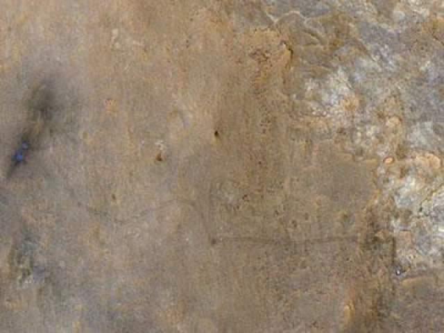 27 июня 2013 года. Фотография с HiRISE - камеры, установленной на борту космического аппарата Mars Reconnaissance Orbiter для изучения Марса, находящегося на орбите планеты. Голубая точка справа - марсоход Curiousity, синеватые точки слева - место его посадки. По следам можно увидеть путь, который проделал марсоход.