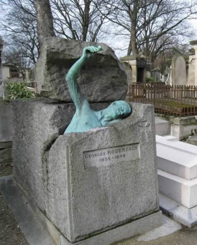 Бельгийский писатель Жорж Роденбах похоронен под могильным камнем, из которого будто выходит его бронзовая копия с розой в одной руке.