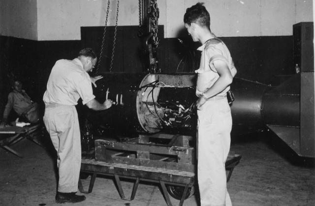 """На этом снимке командир А.Ф. Бирч ставит номер на бомбу под кодовым названием """"Малыш"""" перед погрузкой ее на трейлер, который доставит ее на борт бомбардировщика B-29 Superfortress """"Enola Gay""""."""