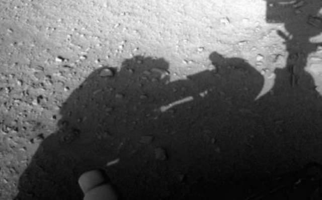 Человеческая тень на фотографии с Марса Еще одна невероятная новость с Марса недавно потрясла Интернет. На фотографии, снятой планетоходом, отчетливо видна тень человека, стоящего рядом с аппаратом. Уфологи рассмотрели у предполагаемой фигуры рюкзак за спиной и взъерошенные волосы.