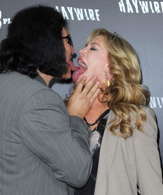 Музыкант группы KISS Джин Симмонс с супругой часто смущают репортеров поцелуями в стиле сценических выходок Джина.
