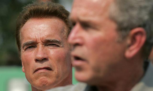 Арнольд Шварцнеггер окидывает Джорджа Буша, стоящего между ним и камерой, тяжелым взглядом.